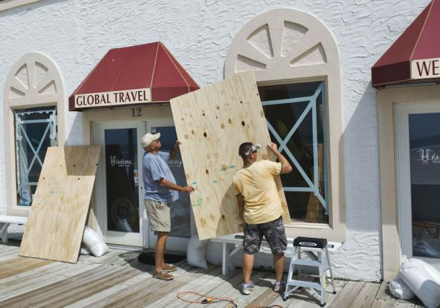 Men board up windows of their beachside property as they prepare for Hurrican Irene in Atlantic Beach
